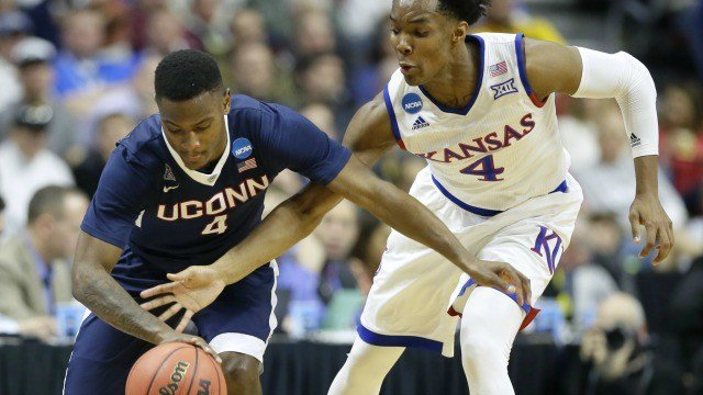 Kansas guard Devonte' Graham, right, tries to steal the ball from Connecticut guard Sterling Gibbs during the first half of a second-round men's college basketball game in the NCAA Tournament, Saturday (AP Photo/Charlie Neibergall)