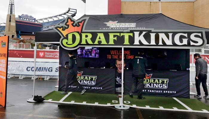In this Oct. 25, 2015, photograph, workers set up a DraftKings promotions tent in the parking lot of Gillette Stadium, in Foxborough, Mass. (Source: AP Photo/Charles Krupa)