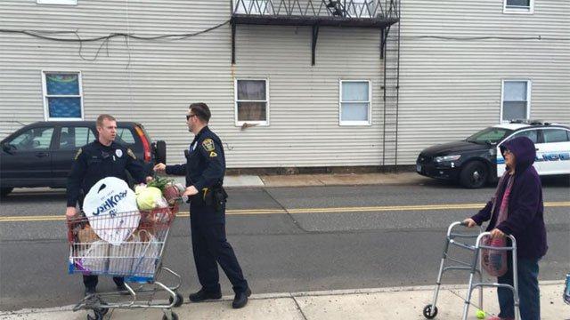 Officer helps woman with her groceries after crash. (Naugatuck Police Department)