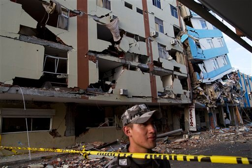 An air force soldier stands guard trying to prevent looting in the earthquake ravaged business district of Manta, Ecuador on Monday.  (AP Photo/Rodrigo Abd)