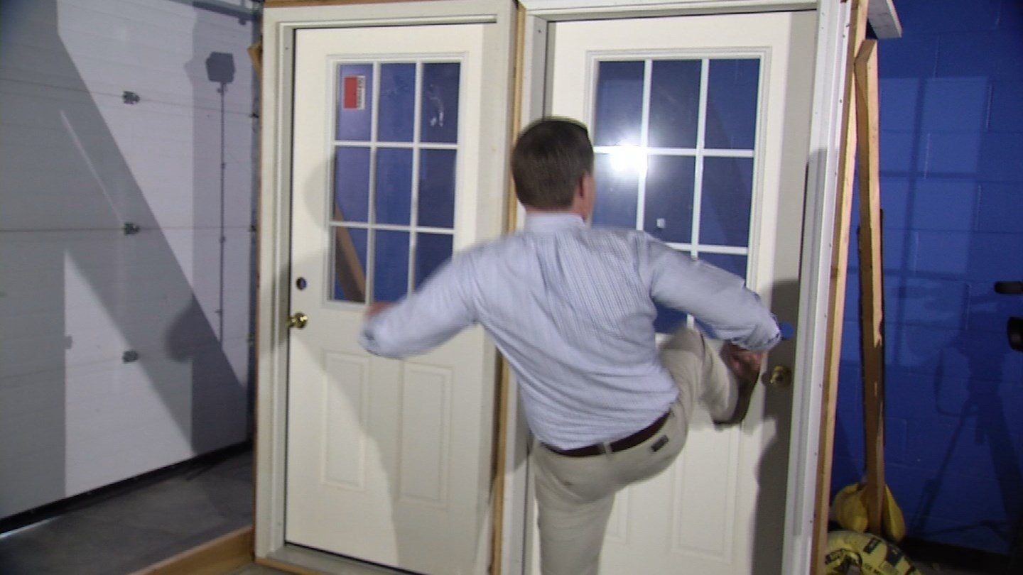 Eric Parker of the I-Team tests out how well screws protect doors. (WFSB photo)