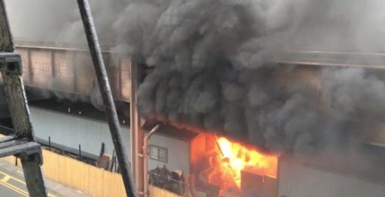 Flames shoot out from under the Metro North rails Tuesday night. (CBS News)