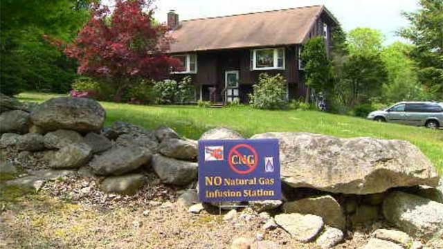"Signs dot many homes on Route 6 saying ""No natural gas infusion station."" (WFSB)"