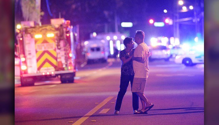 Family members wait for word from police after arriving down the street from a shooting involving multiple fatalities at Pulse Orlando nightclub in Orlando, Fla., Sunday, June 12, 2016. (AP Photo/Phelan M. Ebenhack)