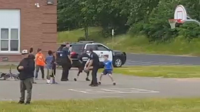 Two officers play basketball with children at the Waddell School in Manchester. (Michelle Farell-Crandall/iWitness photo)