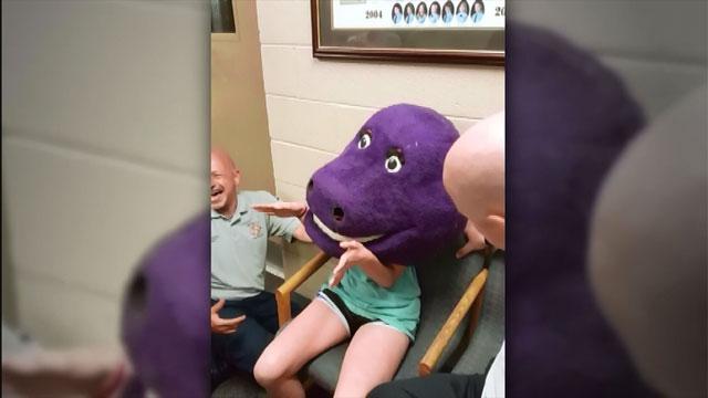 Teen girl's head gets stuck in a Barney costume. (CNNNewsource)