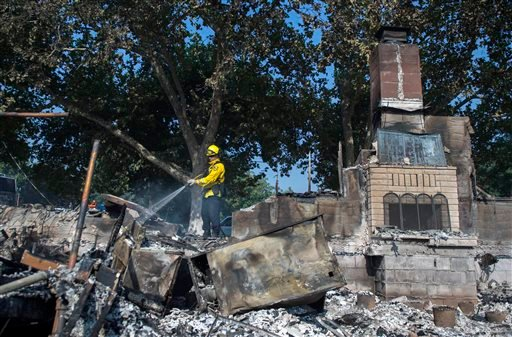 (Hector Amezcua/The Sacramento Bee via AP). Dan Peters, with the Nevato Fire District, mops up a fire at a house during the Clayton fire after structures were destroyed in Lower Lake, Calif., Monday, Aug. 15, 2016.