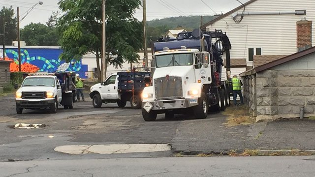 Crews are on the scene after an abandoned outside oil tank in Torrington overflowed into the Naugatuck River on Monday morning. (WFSB)
