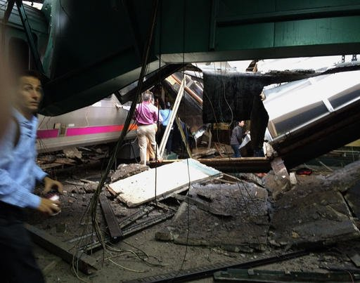 (William Sun via AP). In a photo provided by William Sun, people examine the wreckage of a New Jersey Transit commuter train that crashed into the train station during the morning rush hour.