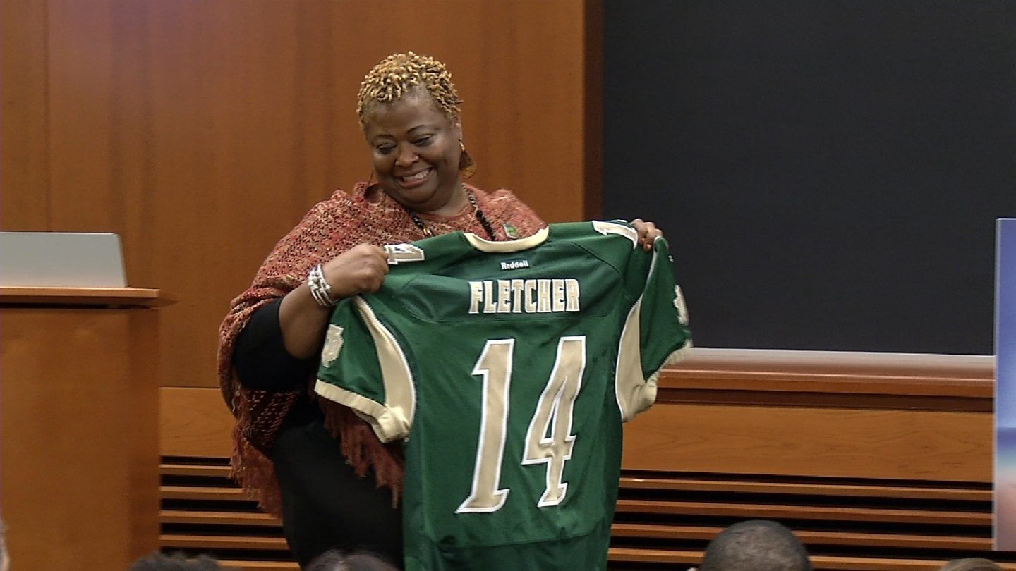 Carolyn Fletcher holds up her son Jerrel Fletcher's jersey. (WFSB photo)