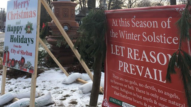 Dueling signs on one town green are causing a little controversy this Christmas season. (WFSB)