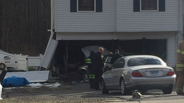 A car crashes into a Milford home on Monday. (WFSB)