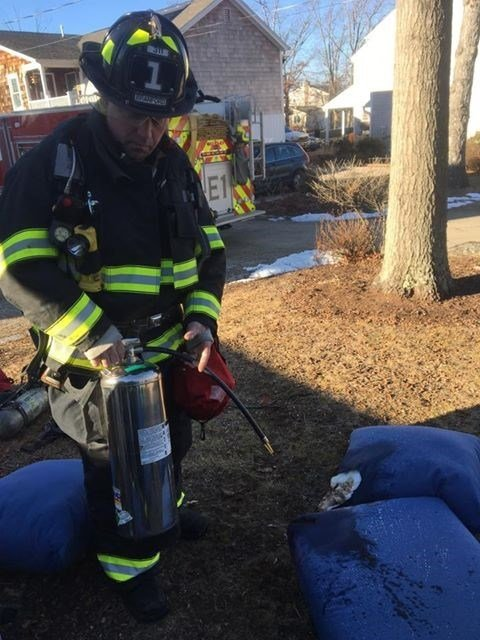 A firefighter makes sure there are no leftover hotspots on a couch which caught fire Saturday.  (Branford Fire Dept. Facebook page)