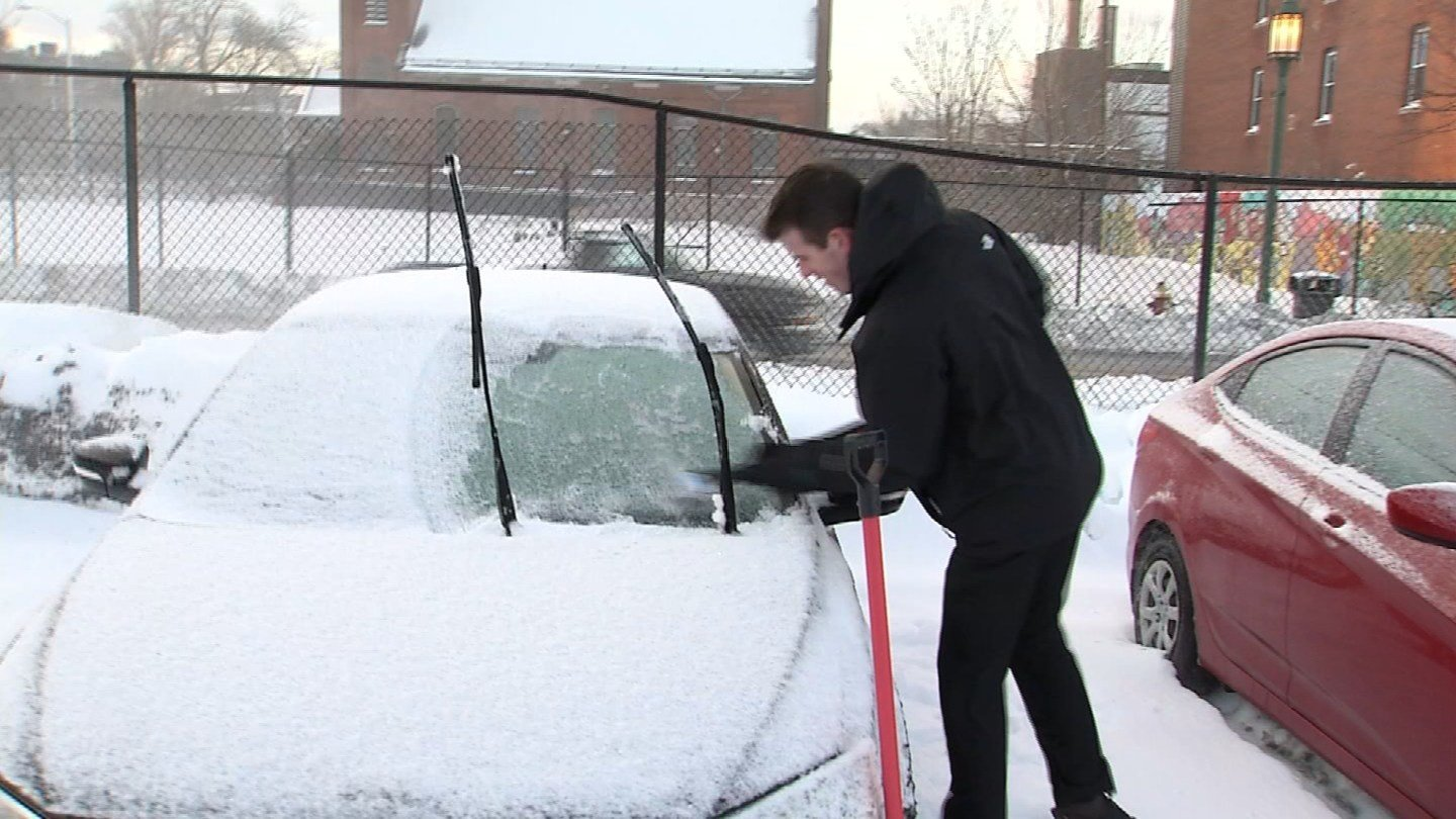 Patrick Talbot scraps ice off of his windshield following Winter Storm Diana. (WFSB photo)