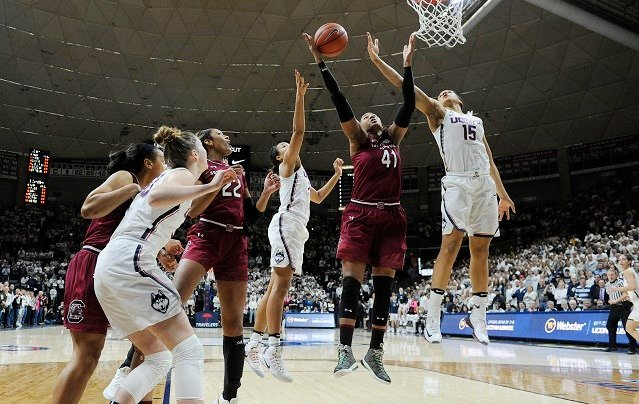 South Carolina's Alaina Coates, center, pulls down a rebound between Connecticut's Napheesa Collier and Connecticut's Gabby Williams, right, in the first half of an NCAA college basketball game (AP Photo/Jessica Hill
