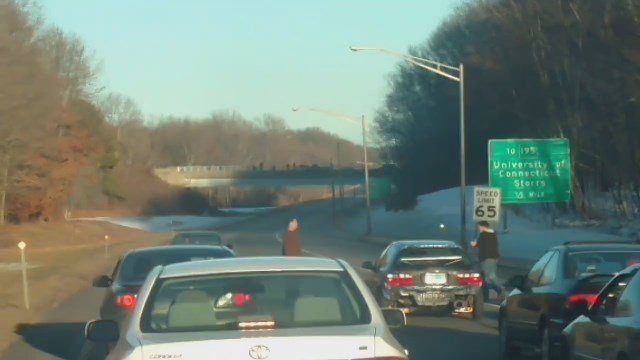 In this photo, two men can be seen stopping traffic for a street race on a Willimantic highway. (Facebook photo)