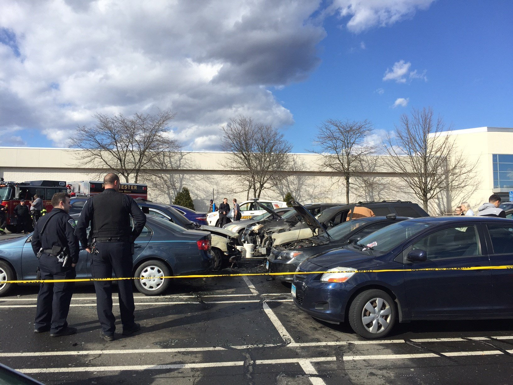 Police investigate the fire damage caused to several cars in the Manchester Buckland Hills parking lot. (WFSB)