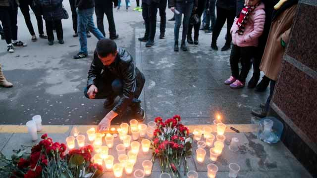 A man lights a candle at an entrance of Sennaya subway station after an explosion on the subway in St.Petersburg, Russia. (AP Photo/Yevgeny Kurskov)