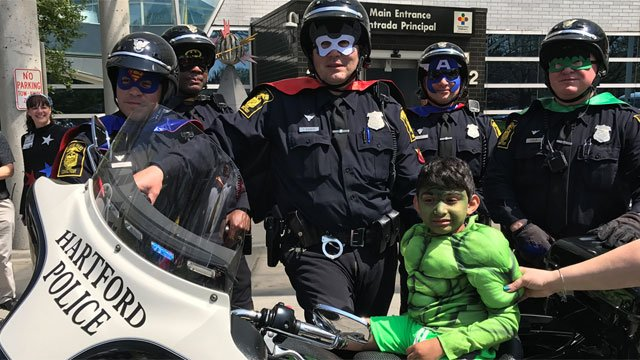 Hartford police officers participated in a superhero parade for CCMC patients.  (WFSB)