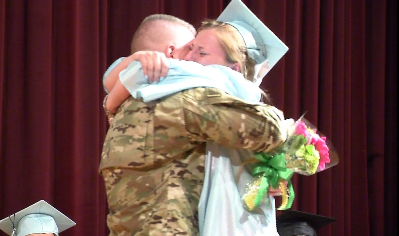 Sergeant Smith hugs his daughter after having presented her diploma. (WFSB)