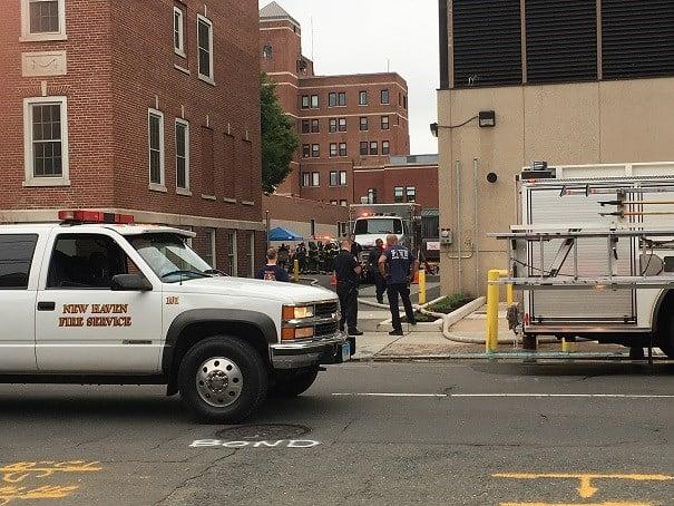 Several emergency crews work outside an entrance of St. Raphael's hospital after a hazmat situation.  (WFSB)