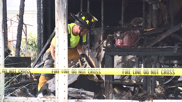A Vernon firefighter works to extinguish hot spots inside the now condemned mobile home. (WFSB)