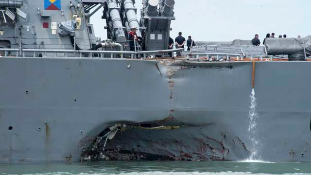 Damage is visible as the guided-missile destroyer USS John S. McCain steers towards Changi naval base in Singapore following a collision with the merchant vessel Alnic MC. (Mass Communication Specialist 2nd Class Joshua Fulton/U.S. Navy photo via AP, File