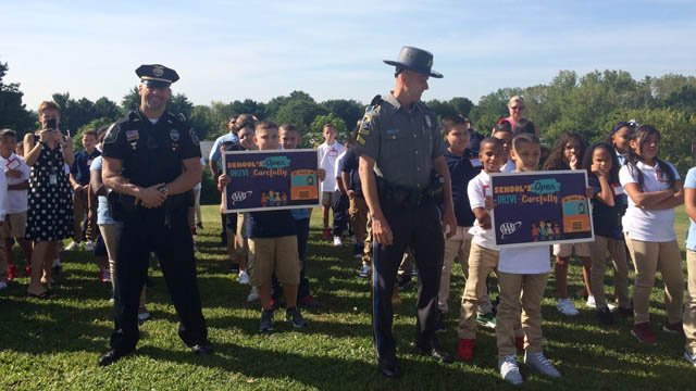 Connecticut State Police troopers and New Britain police officers welcome students back to school at the Smith School. (State police)