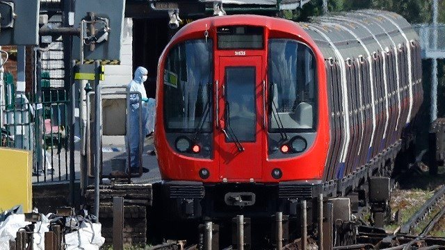 A police forensic officer stands beside the train where an incident happened, that police say they are investigating as a terrorist attack, at Parsons Green subway station in London, Friday, Sept. 15, 2017. (AP Photo/Frank Augstein)