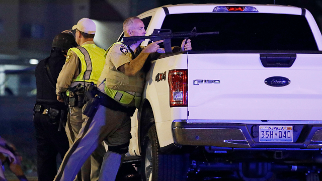 A police officer takes cover behind a truck at the scene of a shooting near the Mandalay Bay resort and casino on the Las Vegas Strip, Sunday, Oct. 1, 2017, in Las Vegas. (AP)