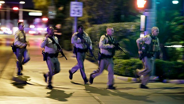 Police run to cover at the scene of a shooting near the Mandalay Bay resort and casino on the Las Vegas Strip, Sunday, Oct. 1, 2017, in Las Vegas. (AP)