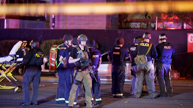 Police officers and medical personnel stand at the scene of a shooting near the Mandalay Bay resort and casino on the Las Vegas Strip, Monday, Oct. 2, 2017, in Las Vegas.  (AP Photo/John Locher)