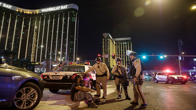 Police officers stand at the scene of a shooting near the Mandalay Bay resort and casino on the Las Vegas Strip, Sunday, Oct. 1, 2017, in Las Vegas.  (AP Photo/John Locher)