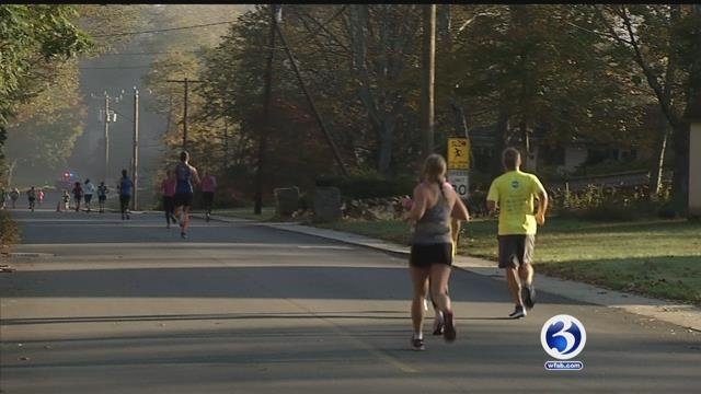 Family and friends watch as runners cross the halfway point at the first annual Essex Steam Train half-marathon.