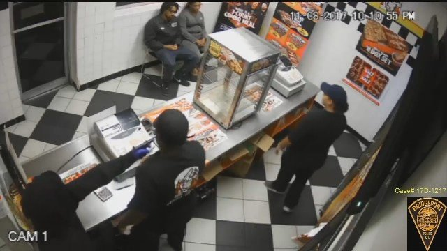 A robbery suspect holds a gun to the head of a Little Caesar employee. (Bridgeport Police Department)