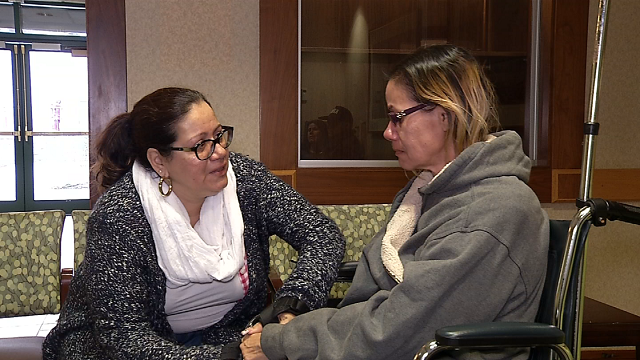 Janet Santos comforts her sister, Jacqueline, whose son recently passed in a house fire. (WFSB)