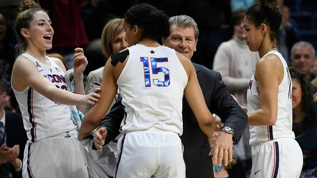 Connecticut head coach Geno Auriemma, center, and player Katie Lou Samuelson, left, smile as seniors Gabby Williams, center, and Kia Nurse leave play for the final time in regular season play. (AP)