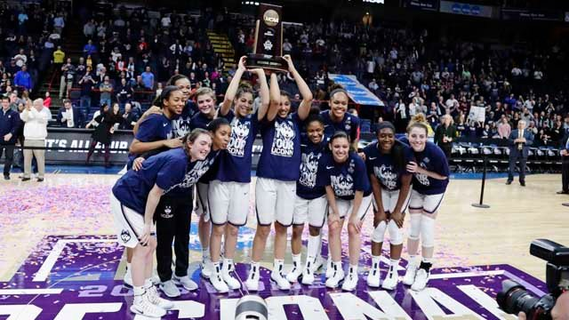 UConn players pose with the regional championship trophy after defeating South Carolina in Albany. (AP)