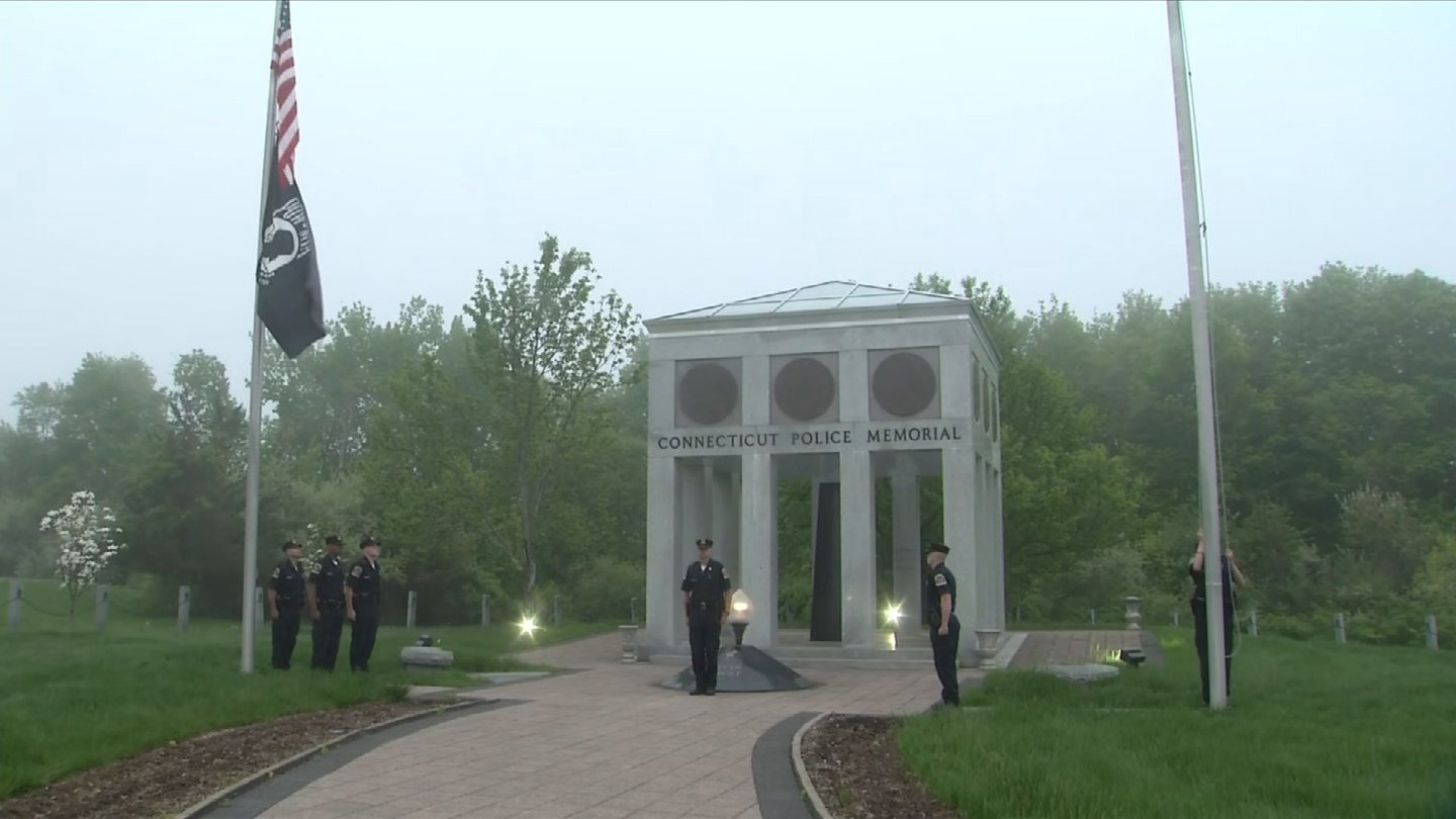 Officers raise the flags at the Police Officers Memorial in Meriden on national Peace Officers Memorial Day. (WFSB)