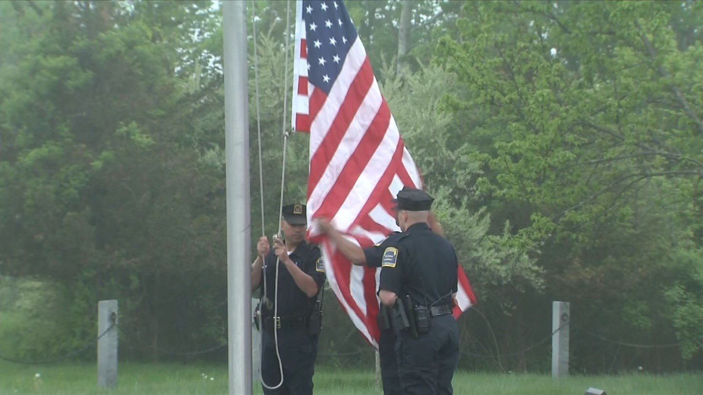 Officers raise the flags at the Police Officers Memorial in Meriden on national Peace Officers Memorial Day