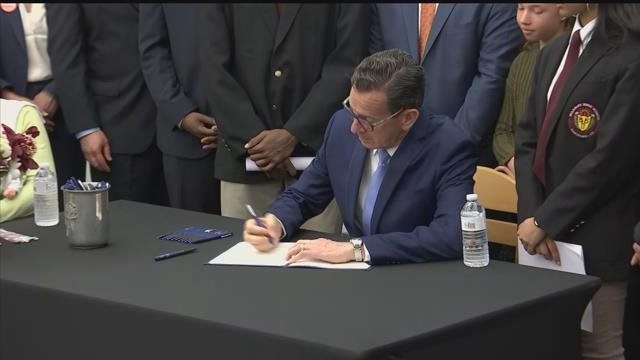 Gov. Dannel Malloy signed his bump stock ban into law just before noon at Bulkeley High School in Hartford. (WFSB)