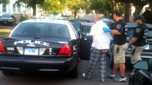A man in Middletown is seen being led to a police cruiser after the execution of a search warrant on Wednesday morning.