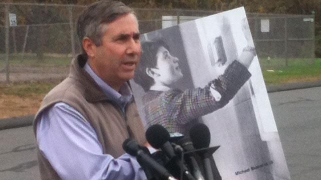 © John Skakel speaks outside prison, while holding photo of Michael Skakel at age 15.