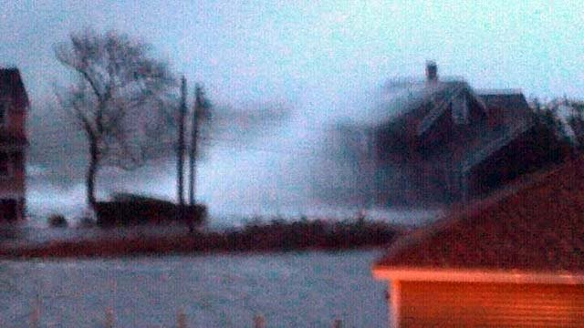 Waves crash against a house during Hurricane Sandy