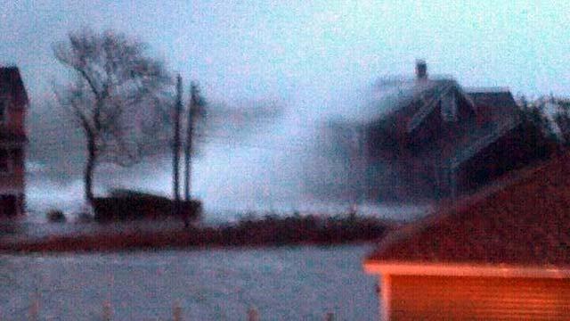 Waves crash against a house during Hurricane Sandy