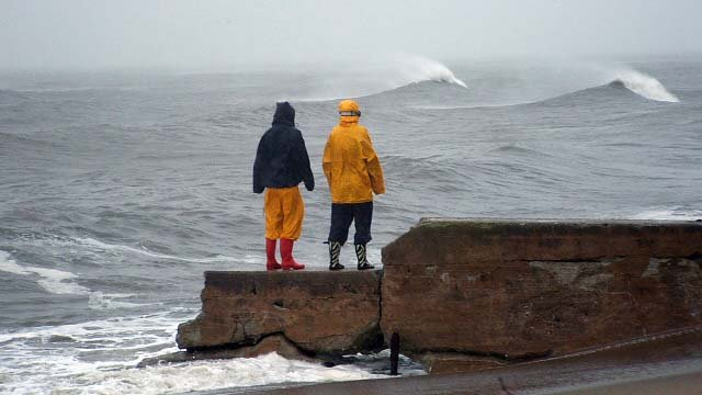 People watch waves crash along the shore during Hurricane Sandy.