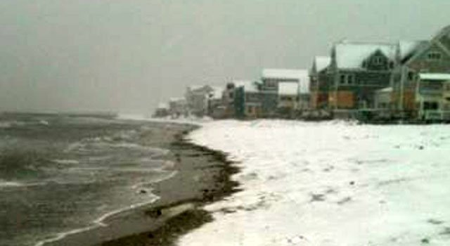 © Snow falls at a beach in Milford.