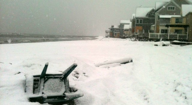 © Snow blankets a chair on the beach in Milford.