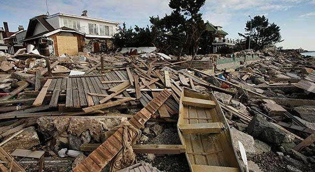 © A twisted metal boat and a paddle, lower right, are among the debris in front of a beachfront home in the Manhattan Beach neighborhood of the Brooklyn borough, Monday, Nov. 5, 2012. (AP Photo/Mark Lennihan)