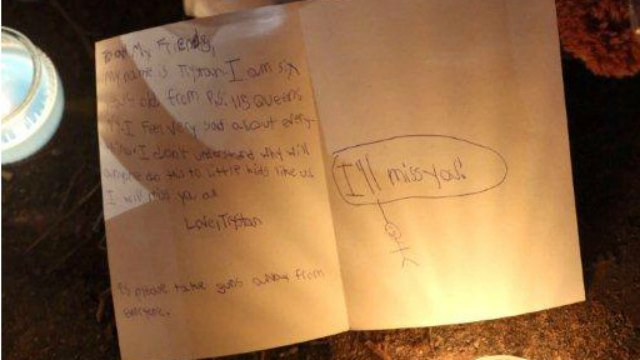 A personal note from a child is placed on a memorial for the victims (AP Photo/Mary Altaffer)